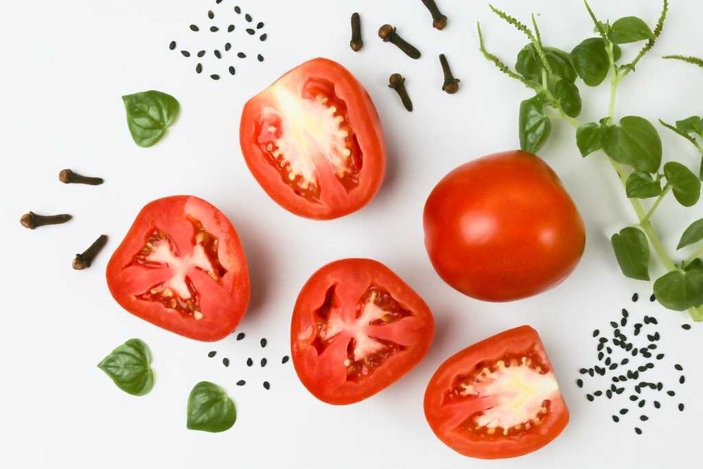 tomato halves surrounded by basil leaves and peppercorns